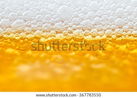 Beer with foam in transparent glass. Abstract Macro