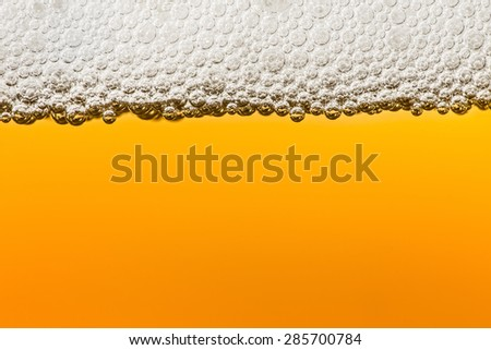 Beer with foam in transparent glass. Abstract Macro. Minimalism - stock photo