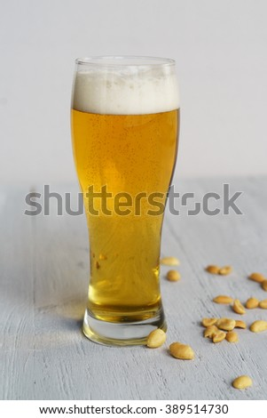 Beer with peanuts on a gray table - stock photo