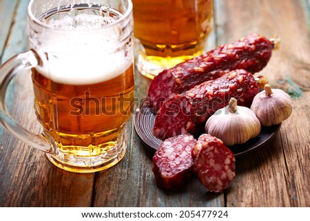Beer with salami over wooden background - stock photo
