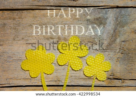 beeswax, three flowers on wooden table, text happy birthday - stock photo