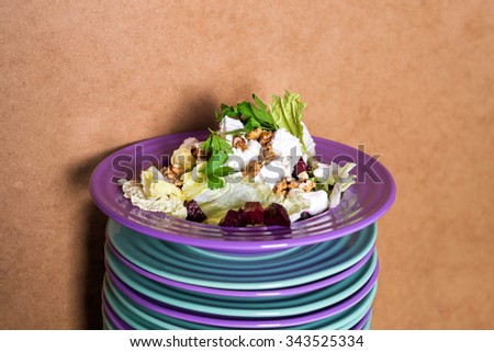 Beet salad with goat cheese, walnuts, greens and herbs and olive oil on a bright colorful ceramic plates stacked. Portion of salad on the background of cardboard with space for your text or menu - stock photo