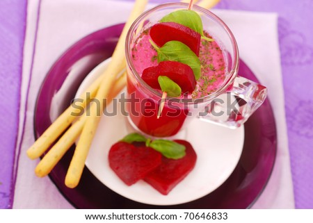 beet soup with cream and grissini (  red borscht ) in glass decorated with heart shaped slices