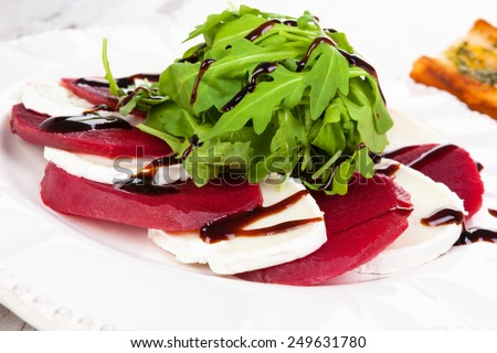 Beet with goat cheese and fresh salad close up. Culinary delicious healthy eating. - stock photo
