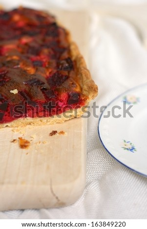 Beetroot (Beta vulgaris) pie with feta cheese, cooking cream  and eggs on a wooden cutting board on white table cloth  - stock photo