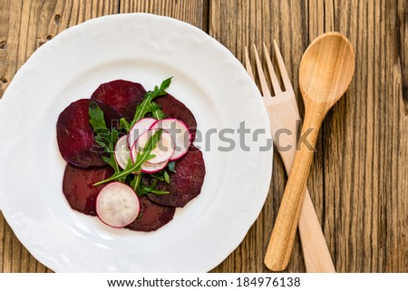 Beetroot radish carpaccio on white plate viewed from above - stock photo