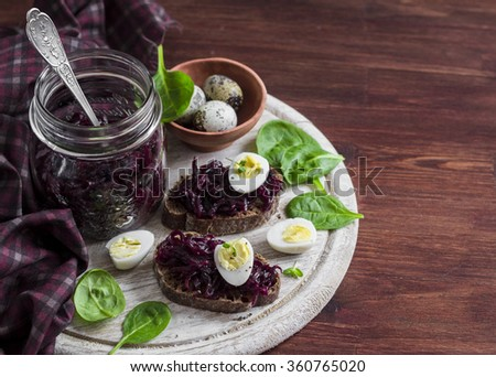 Beetroot relish and a sandwich with beets, quail egg and spinach on rustic light wooden board. Healthy food - stock photo