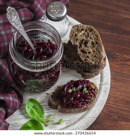 Beetroot relish and slices of rye bread on rustic wooden board. Healthy breakfast or snack. Delicious vegetarian food
