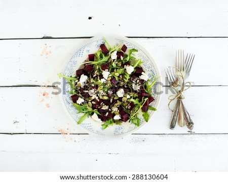 Beetroot salad with arugula, feta cheese and pumpkin seeds in vintage plate over white rustic wooden background, top view - stock photo
