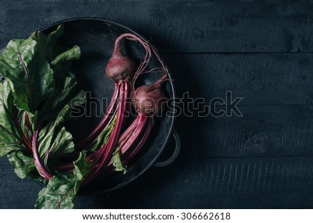 Beets with green tops in a black iron pan on a black wooden background  - stock photo