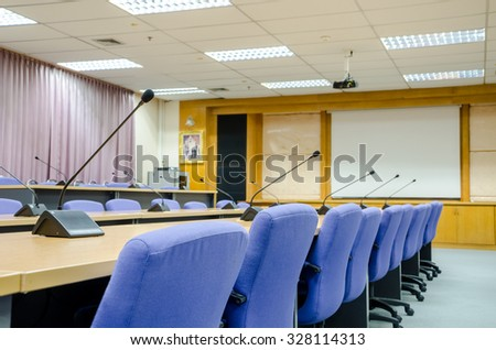before a conference, the microphones in front of empty chairs in meeting room.