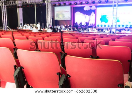 Before the show begins in the theater. There are many red empty chairs