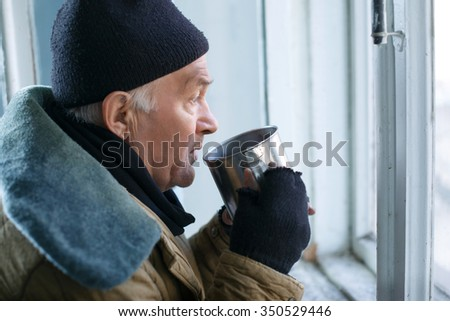 Beggar and cup. Sorrowed old-aged homeless man standing at the window and drinking something from his iron cup.