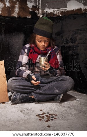 Beggar child boy reviews the money he received looking into tin can - stock photo