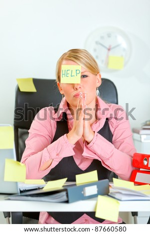 Begging for help female manager sitting at workplace covered with sticky notes - stock photo