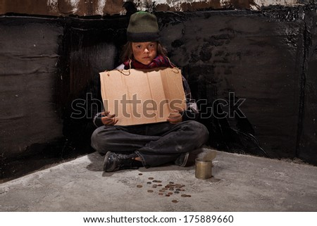 Begging homeless child sitting with a blank sign and some change in a dark corner - stock photo
