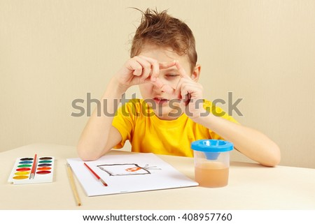 Beginner artist in a yellow shirt painting colors from nature - stock photo