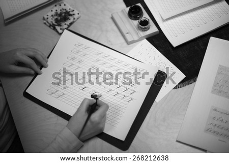 Beginner writing a calligraphy alphabet - stock photo