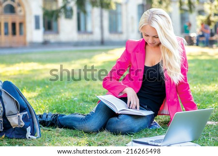 Beginning of the school year. Beautiful girl-student reads books while sitting on the grass against the building of the university. - stock photo