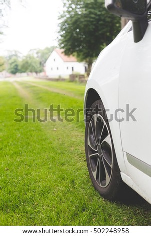 behind side view on modern car wheel of white automobile standing on green grass lawn on countryside