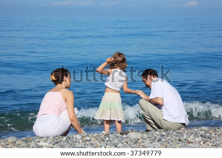 behind sitting family with little girl on edge of sea - stock photo