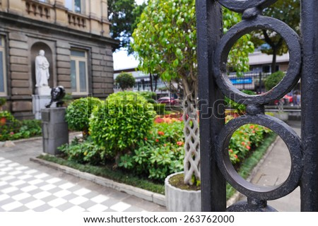 Behind the iron gate is the garden pathway into the National Theater in San Jose, Costa Rica. - stock photo