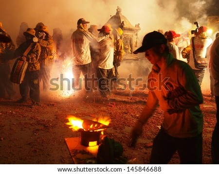 BEIGANG, TAIWAN-APRIL 29: The parade for Matsu's Birthday is hosted on April 29, 2013 in Beigang, Taiwan. Residents bomb deity palanquins with firecrackers fired by a piece of hot iron on a stove.  - stock photo