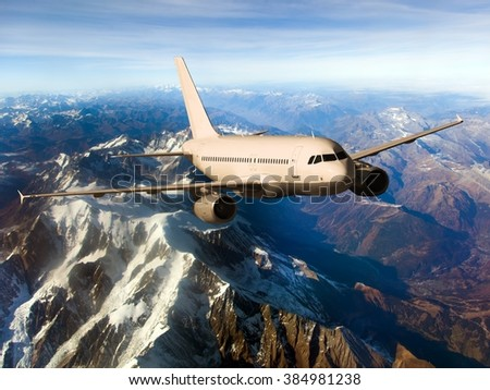 Beige aircraft with gray Engines. The plane flies over snow-capped mountains. - stock photo