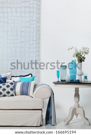 Beige and blue sofa and a coffee table - stock photo