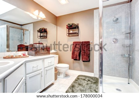 Beige and white bathroom with glass door shower, tile floor and green soft rug. Decorated with burgundy towel, antique chest and wall shelf - stock photo