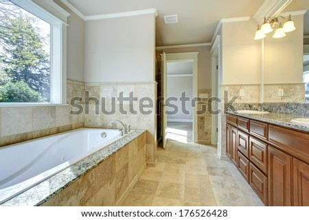 Beige and white bathroom with tile floor, window and wooden storage combination