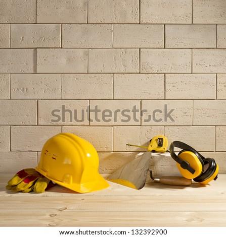 beige brick background, yellow helmet and trowel on a wooden floor - stock photo