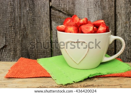 Beige ceramic cup decorated with heart shape pattern full of ripe tasty strawberry on green and orange napkins in a rustic setting. Simple colorful composition with copy space - stock photo