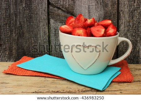 Beige ceramic cup decorated with heart shape pattern full of ripe tasty strawberry on linen napkin in a rustic wooden setting. Simple colorful composition with copy space - stock photo