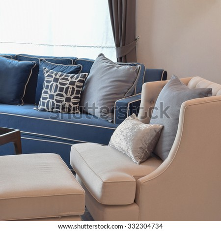 beige classic sofa and blue pattern pillows in warm living room - stock photo