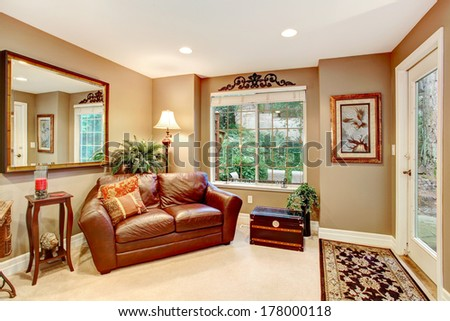 Beige color entrance hall with leather couch and antique chest. Decorated with big mirror and flower pots - stock photo