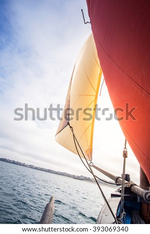 beige cotton jib sail and an ocher sail filled by the wind with wooden mast, bowsprit and hull of an old rigging sailing boat during a sunny sea trip in brittany - stock photo