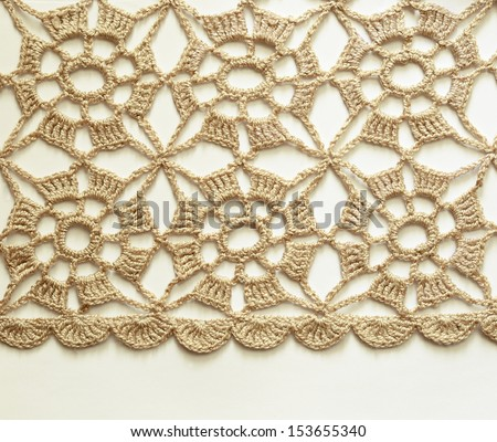 Beige crochet lace on white background - stock photo