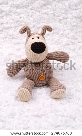 Beige crocheted bear sitting on the white cloth - stock photo