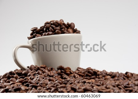 Beige cup of coffee filled of coffee beans.