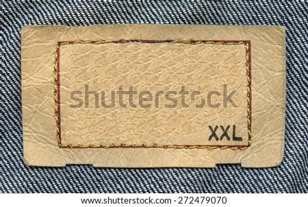 beige  leather label on denim background, size - stock photo