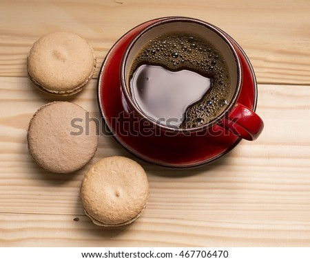 Beige macaroons and red cup of coffee on a light wooden background