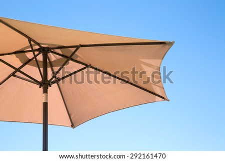 Beige parasol on a clear blue sky - stock photo