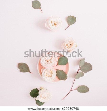Beige roses and eucalyptus branches on pale pastel pink background. Flat lay, top view. Floral texture background.