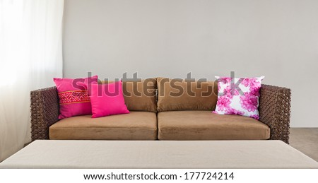 Beige sofa with colourful pillows in simple setting - stock photo