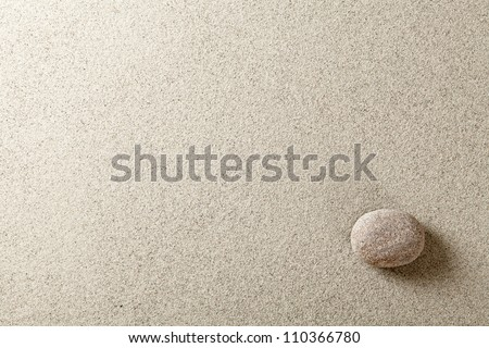 Beige stone at right side of sand background - stock photo
