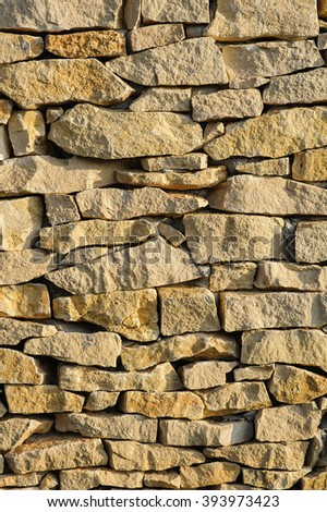 Beige stone wall surface texture in sunlight as background image