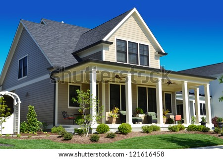 Beige Suburban American Cape Cod Home with Large Front Porch - stock photo