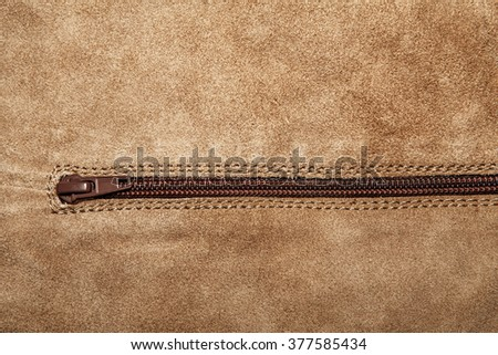 Beige suede soft leather as texture background. Old leather. Brown chamois texture. Fluffy and soft shammy-leather. Close up shammy leather texture with zipper - stock photo
