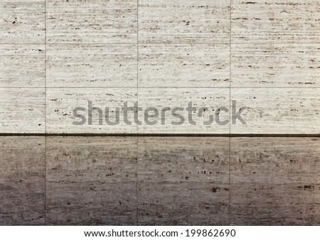 Beige textured travertine wall and reflection in a water. Barcelona  Pavilion close-up